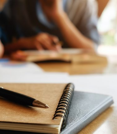 Education concept. Student studying and brainstorming campus concept. Close up of students discussing their subject on books or textbooks. Selective focus.